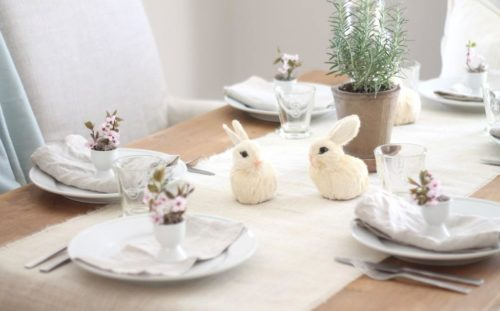 An Easter table setting featuring a burlap runner, small grass bunnies, pretty glassware and white plates.