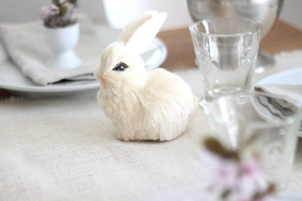 A small textured Easter bunny on a spring table setting, placed on top of a burlap tablecloth.
