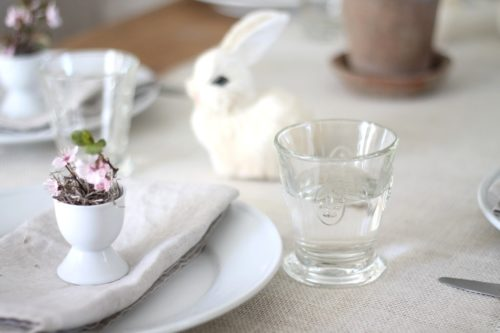 An Easter table setting featuring a burlap runner, pretty glassware and white plates.