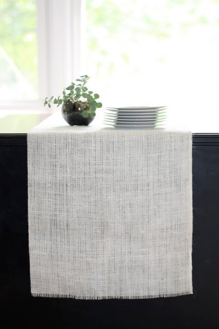 A small plant and white plates on a dining room table.