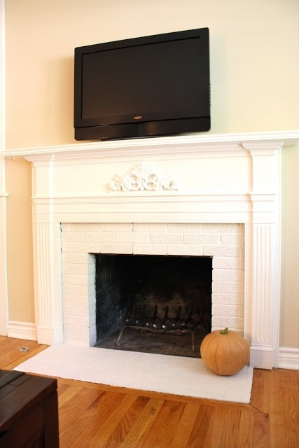 A pumpkin on a white fireplace.