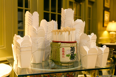 Chinese food boxes and chopsticks on a glass table.