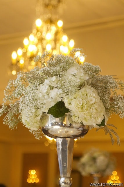 Table centerpieces with white flowers and silver vases.