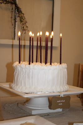 A birthday cake with long, purple, lit candles.
