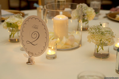Table settings with candle centerpieces and small vases of white flowers.