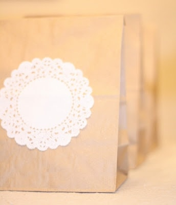 Paper gift bags with mini doilies on the front.