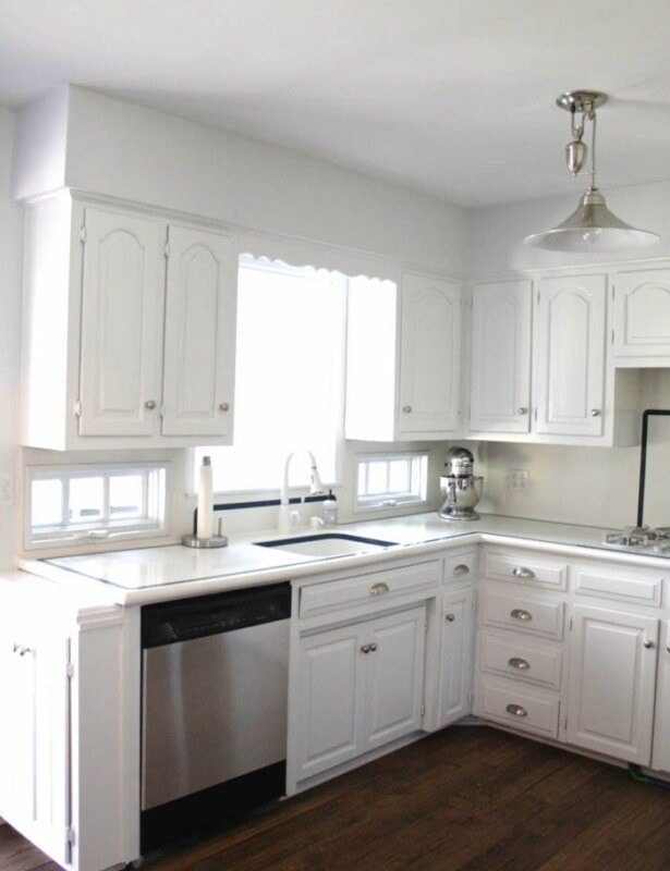 A white kitchen with a wood floor and stainless steel appliances.