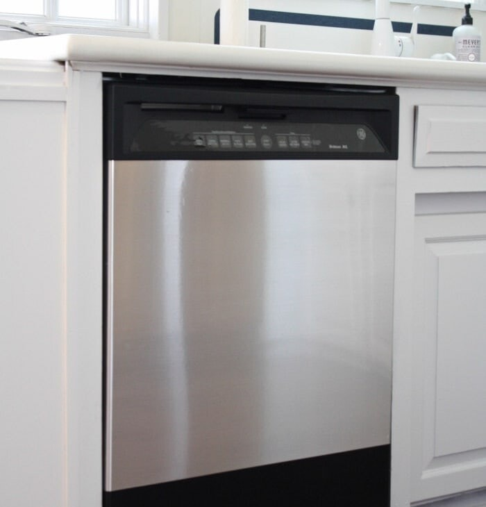 black dishwasher covered with stainless steel contact paper panel