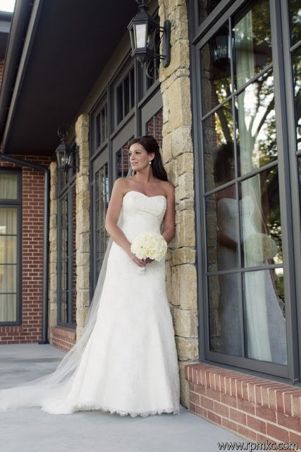 A bride posing against a wall for a picture.