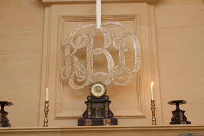 A monogram sign hanging above a clock.