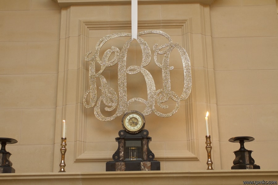 gold glitter monogram hanging by ribbon over fireplace