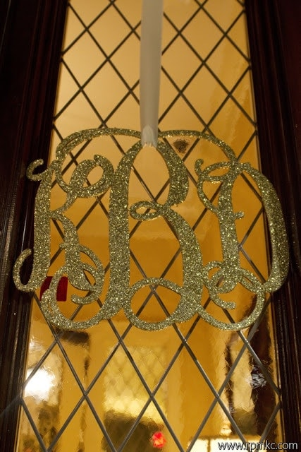 A gold monogram sign hanging on a doorway.