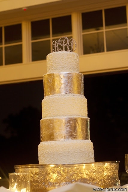 A five layer wedding cake with alternating gold and white layers.