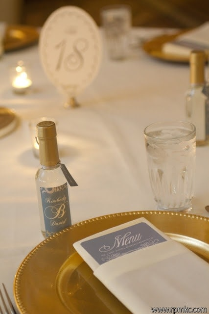 Table settings with gold plates and mini champagne bottles.