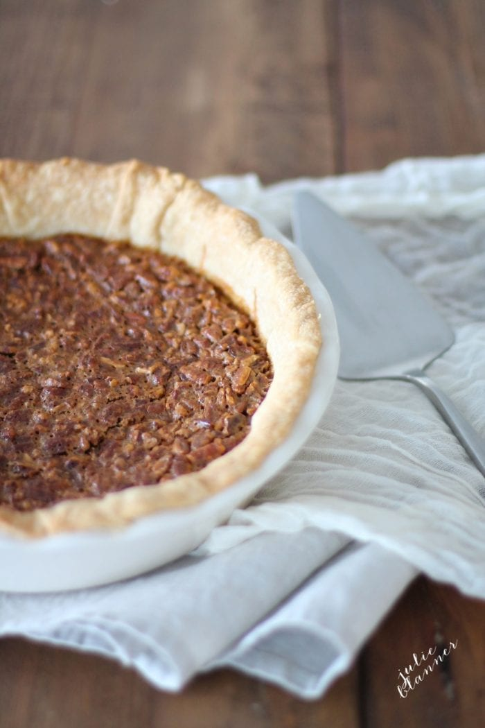 Caramel pecan pie in a white pie pan, a pie cutter to the side.