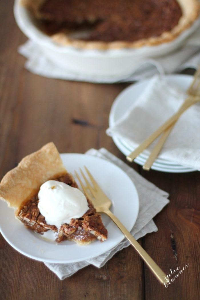 Caramel pecan pie on a white plate and gold fork, topped with whipped cream on a dining room table.