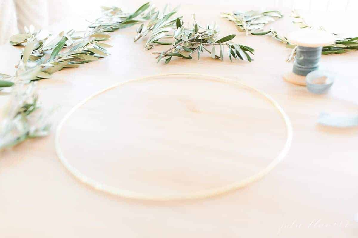 A wood table with a gold hoop and greenery laid out for a DIY wreath.