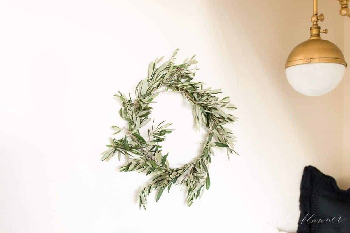 A white wall with a small DIY olive wreath hanging in front of a gold wall sconce.