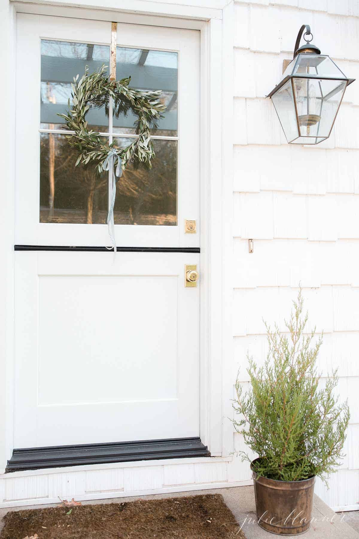 A small handmade olive wreath hangs on the top half of a white dutch door, with a small Christmas tree to the side.