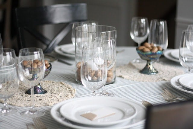 A set Thanksgiving table with white plates and silver silverware, with a name tag on the top of the plates. Wine glasses and walnuts are also on the table.