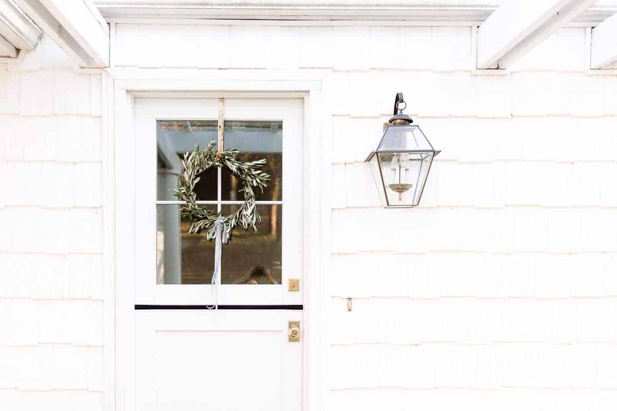 The entryway of a white house with a dutch door, DIY olive wreath hanging on it.