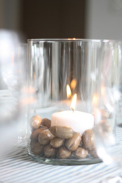 A candle in a vase, surrounded by pecans.