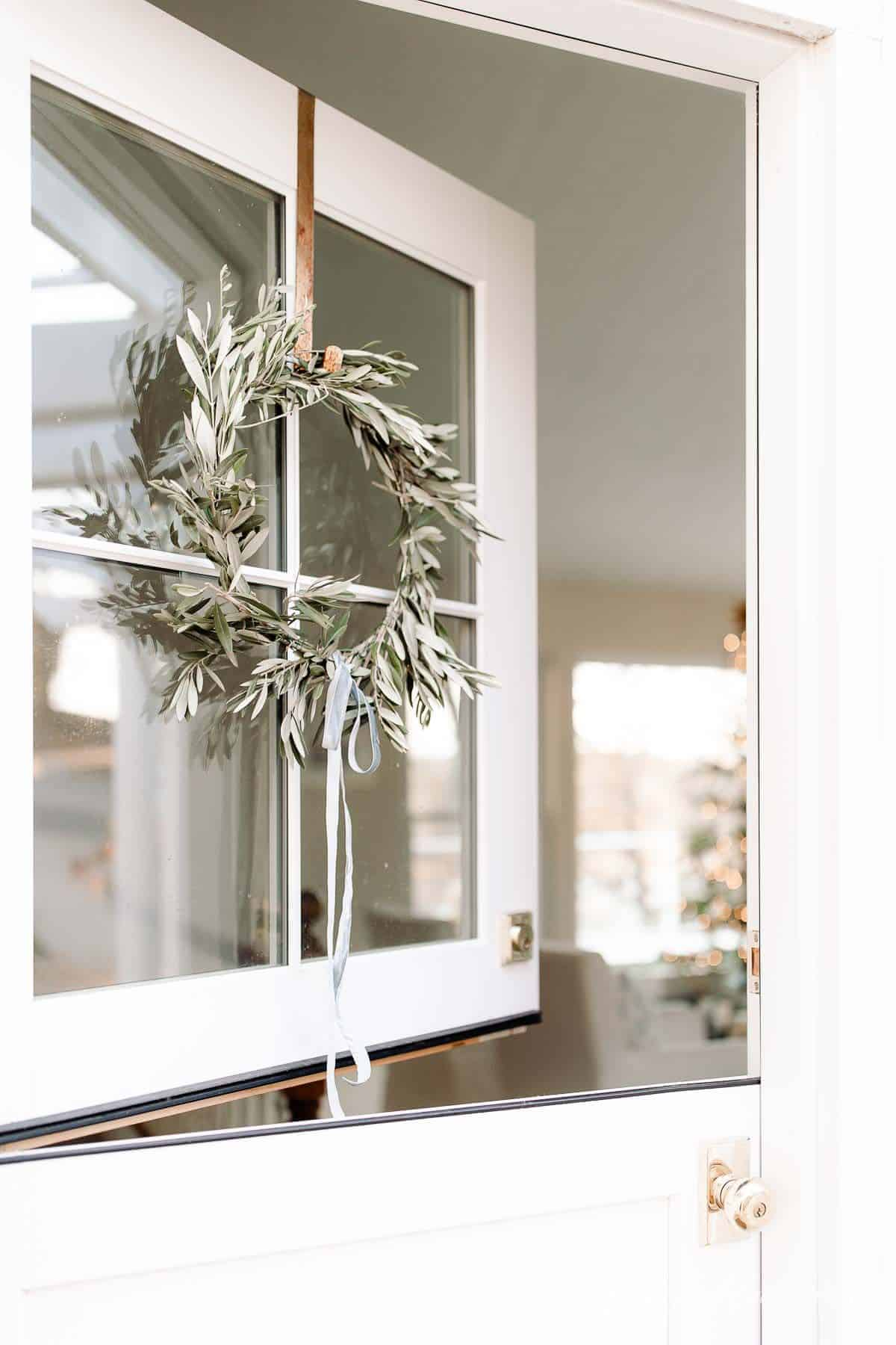 A dutch door with a DIY wreath hanging on the windows, looking into a living room decorated for Christmas.