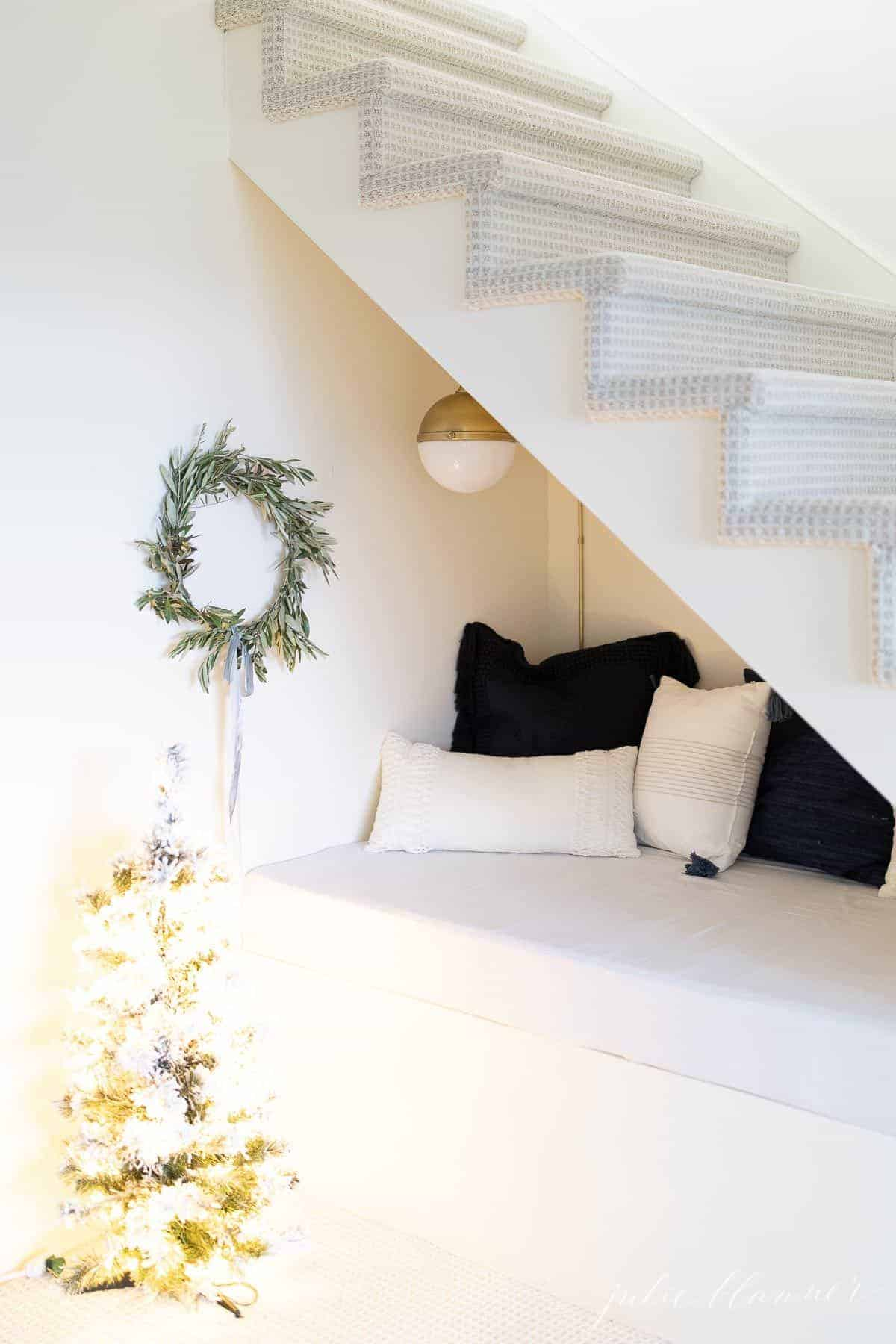 A DIY Christmas wreath hanging in a nook under the stairs piled with blue and white pillows.