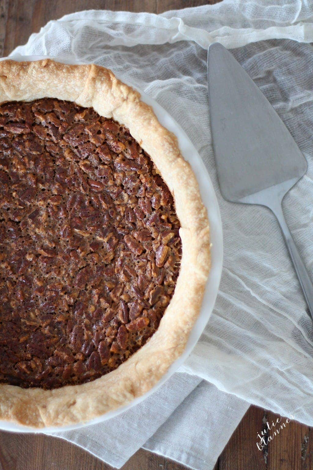 caramel pecan pie recipe in white pie dish with silver serving utensil on white towel
