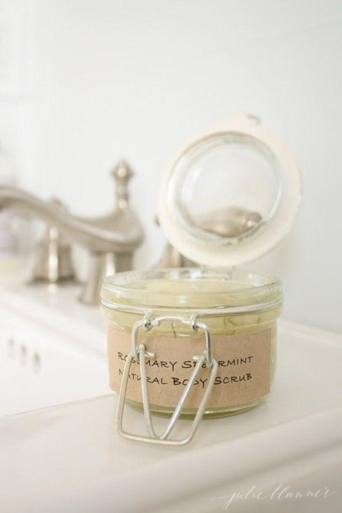 jar of sugar body scrub open on a sink