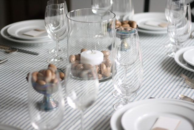 A set thanksgiving table with white plates, candles, and wine glasses.