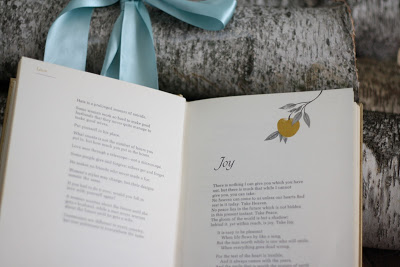 """A book that has a poem titled \""""Joy\"""" with a blue ribbon above it."""