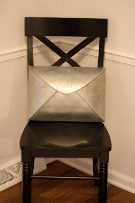 """A black chair with a tin mailbox that says \""""Mail\"""" on it."""