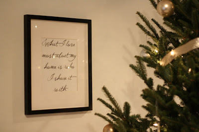 """A christmas tree with a framed image of the words \""""What I love most about my home is who I share it with.\"""""""