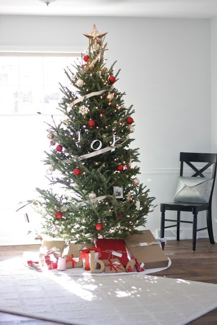 A Christmas tree decorated with silver and red ornaments and streamers, with plenty of presents under the tree.
