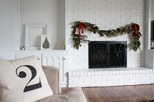 Garland with red ribbons and ice skates draped over a white fireplace.