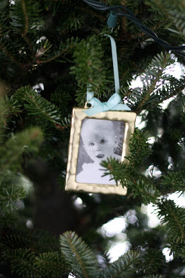 A baby portrait ornament hanging from a tree.