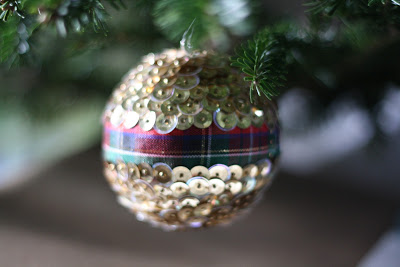 A close up of an ornament covered in gold sequins hanging from a Christmas Tree.