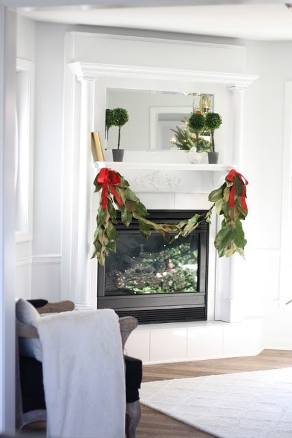 Garland with red ribbons draped over a white fireplace.