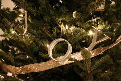 """A close up of \""""Joy\"""" ornaments hanging from a Christmas Tree."""