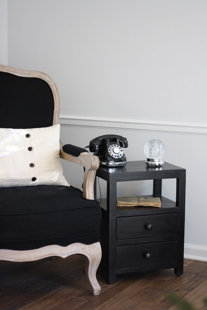 A black chair with a black side table next to it, a phone and snow globe on the table.