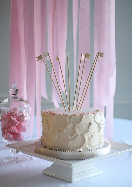 A white birthday cake with little flags sticking out the top, pink streamers behind it.