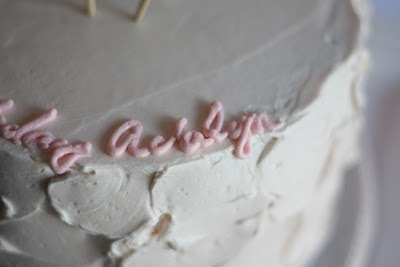 """The name \""""Adalyn\"""" iced onto a birthday cake with pink frosting."""