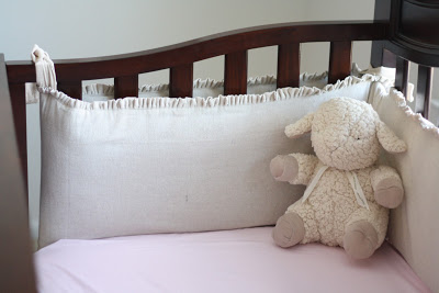 A stuffed lamb in a wooden crib with pink sheets.