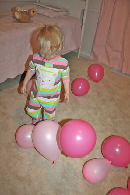 A little girl playing with pink balloons on the floor.