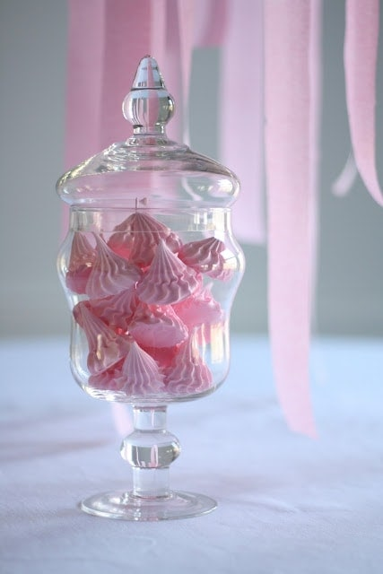 A glass vase on a table, with pink candies inside.