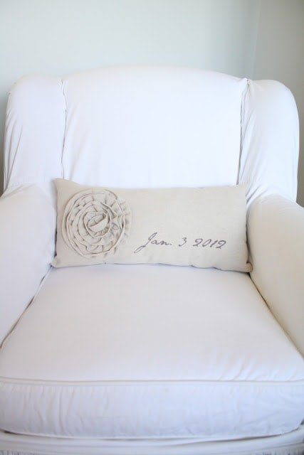 "A beige pillow that has the date ""Jan 3 2012\"" on a white chair."