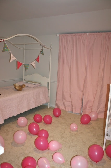 A little girls room that has pink bedsheets and curtains, decorated with pink balloons for her birthday.