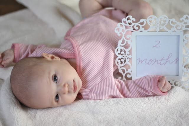 "A baby laying next to a sign that says ""2 months\"""