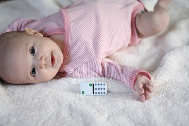 A baby laying next to a domino that has two dots on it.